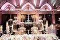 Wedding reception with mirror sweetheart table, tufted armchairs, candelabra, violet lighting