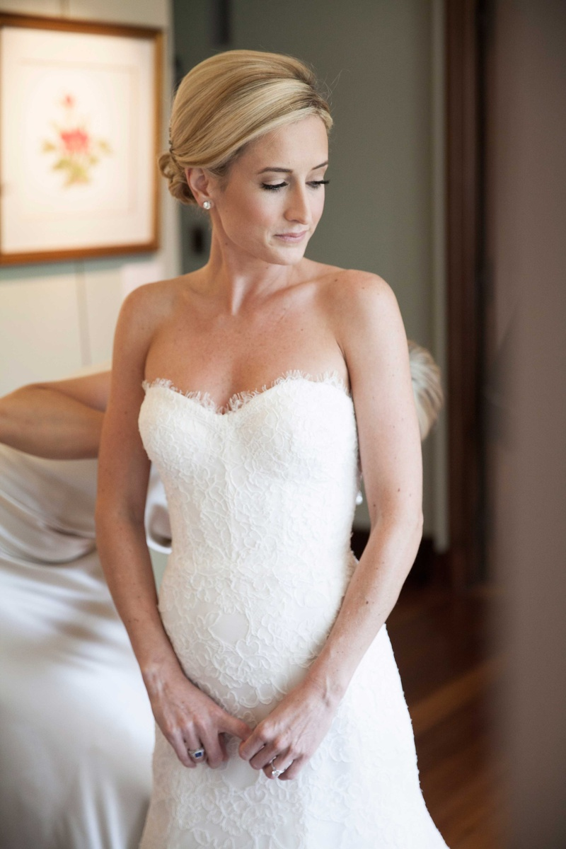 an excited bride gets zipped into her lace Monique Lhuillier wedding gown by one of her bridesmaids