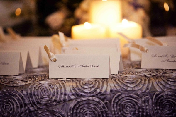 White rectangular escort cards with ivory ribbon