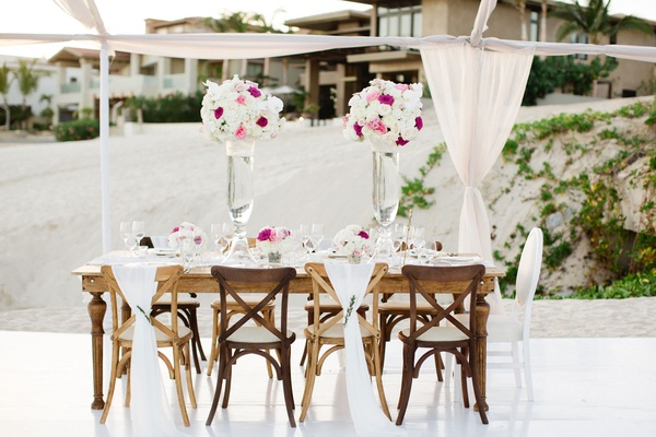 Wood table and chairs with fabric backs and tall arrangements of flowers in blush hot pink and white