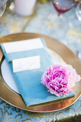 Gold-rimmed charger plate and blue dinner napkin