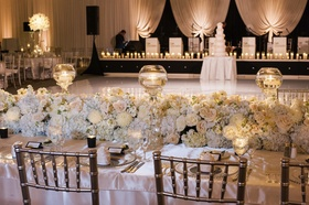Low and lush ivory centerpieces complement a marvelously monochromatic evening.