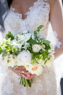 Bride in Monique Lhuillier lace wedding dress holding bouquet with white rose, calla lily and peony