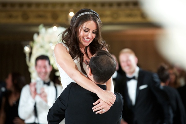 Wedding reception first dance photo of groom picking up bride during dance silver headband