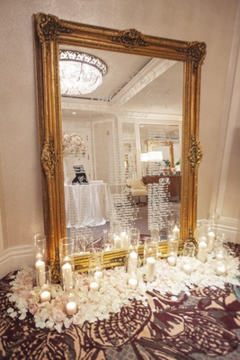 wedding reception seating chart gold frame mirror white calligraphy hurricane candle white pink