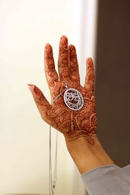 Bride with henna on hand holding diamond pendant