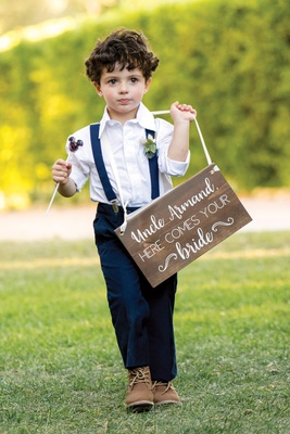 ring bearer in navy pants and suspenders with mickey mouse lollipop wood sign uncle here comes bride