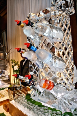 Vodka bottles at wedding chilling in ice sculpture