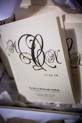Wedding ceremony program with the couple's intials written in calligraphy, gold rhinestones