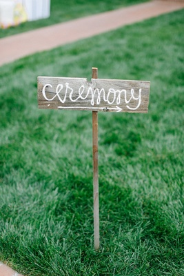 DIY wedding ceremony sign in cursive font on rustic wood