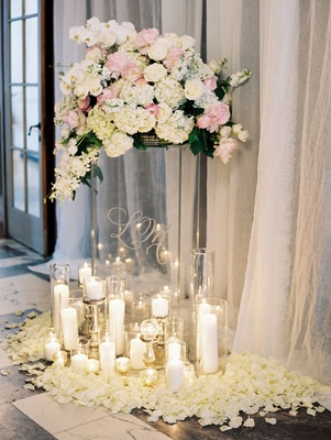Wedding ceremony grouping of candles around clear riser with white and pink flowers on top flowers