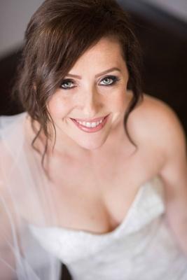 bride smiles up camera makeup beauty pink lips bridal eyeliner mascara black veil sweetheart