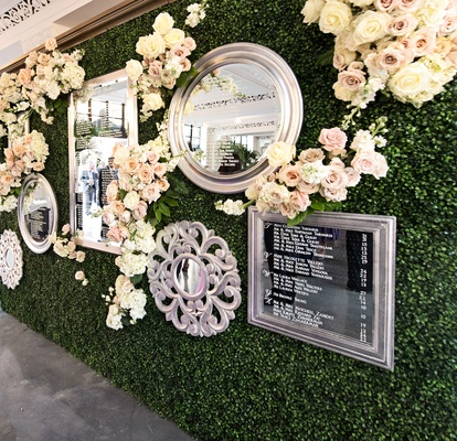 wedding reception green hedge wall flowers mirrors with seating assignments seating chart display