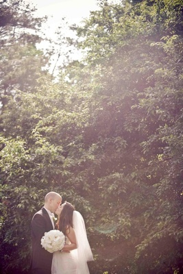 Bride and groom kiss in front of tall hedge in NC