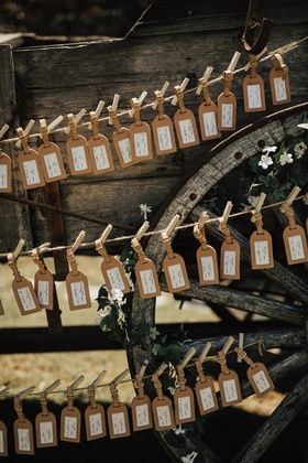 luggage tags as escort cards and wedding favors displayed with clothespins on twine