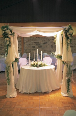 White sweetheart table under fabric canopy