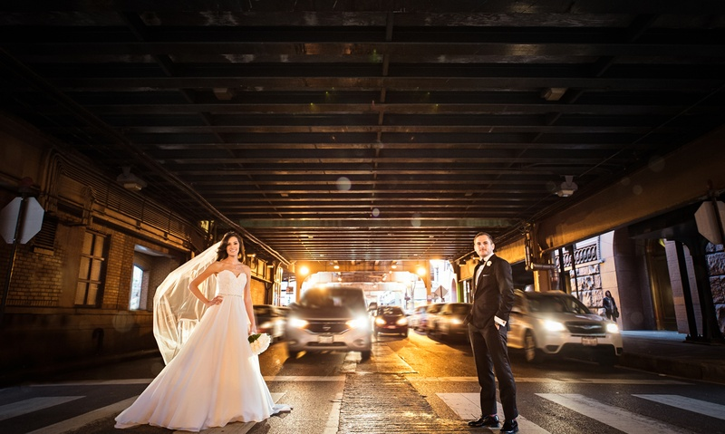 bride in essence of australia wedding dress, groom in bonobos tux, standing in crosswalk in Chicago