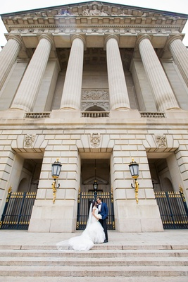 Andrew W. Mellon Auditorium wedding venue couple in front of space on steps in between gold sconces
