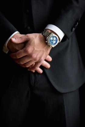 Groom in black tuxedo wears Breitling watch with a dark blue face