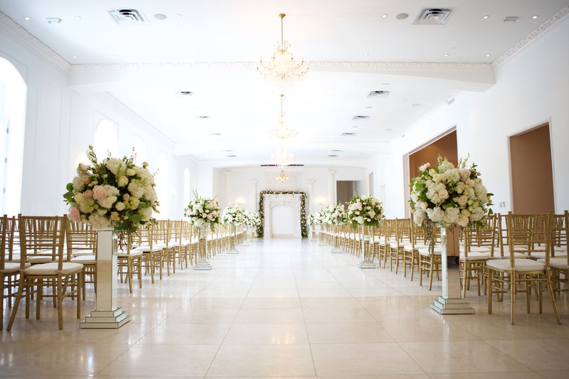 Chateau wedding ceremony white ballroom with mirror risers and pink white green arrangements gold