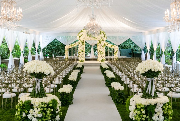 White drapes tent wedding with green hedge and white rose decor chuppah gold chairs chandeliers