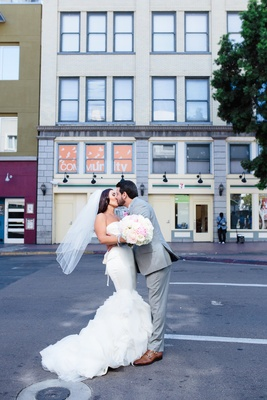 Bride in a strapless Vera Wang dress with ruffled skirt, veil, kisses groom in grey suit on street