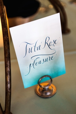 Wedding reception table sign with a Tiffany blue gradient, flower name and meaning in calligraphy
