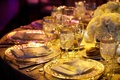 Wedding reception place settings with gold-rimmed glassware and chargers