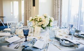 wedding reception ballroom round table low centerpiece ivory flowers blue glassware velvet napkin