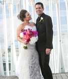 bride fit flare lace gown holding bouquet pink purple white flowers looks at groom black tuxedo