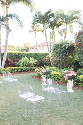 The Confused Millennial ghost chair ceremony chairs with tropical arrangements on risers outdoor