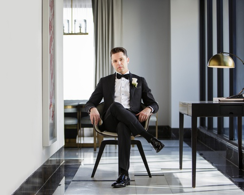 groom in black tuxedo and bow tie sitting in chair