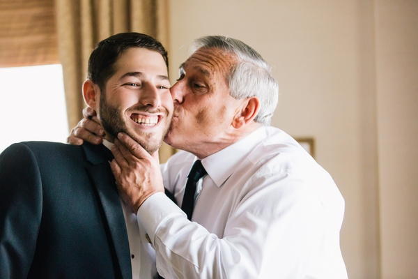 father of the groom kisses his son's cheek