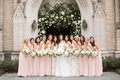 wedding party bridesmaids in strapless pink dresses neutral bouquet in front of ceremony arch