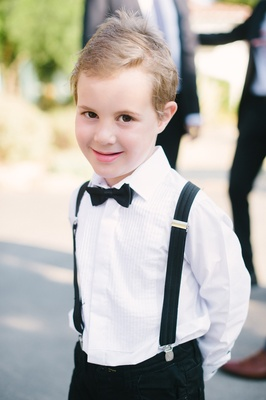 blond ring bearer with black suspenders and bow tie