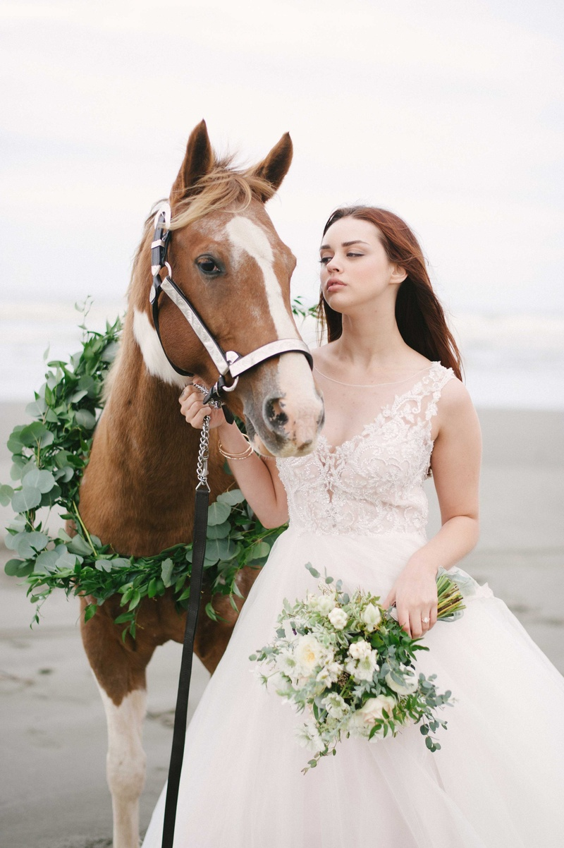bride leads a horse with a green wreath made of foliage on a beach with her bouquet