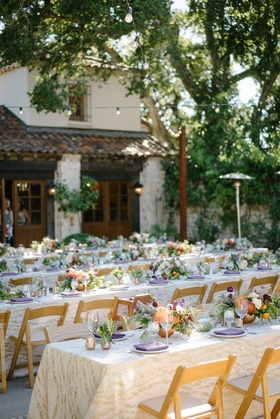 long family style tables with ivory and gold patterned linens, low centerpieces