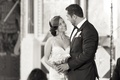 Black and white photo of bride in Inbal Dror dress, birdcage veil holding calla lily bouquet