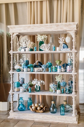 White wash wood book shelf with coral, blue vases, couple's favorite candy and desserts agate slices