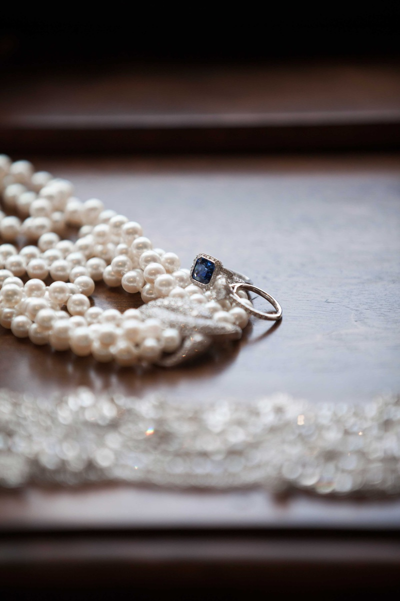 a pearl necklace on a wooden surface next to two lovely rings