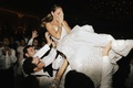 bride in naeem khan wedding dress ponytail being lifted by groom and friends on dance floor