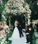 couple kisses under gazebo decorated with cream flowers