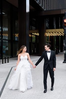 bride in strapless sweetheart neckline wedding dress monique lhuillier ostrich feather overskirt
