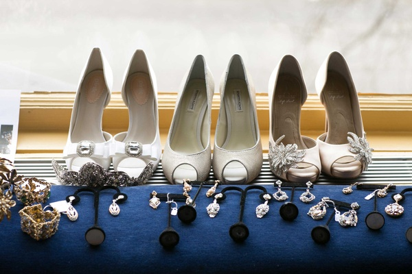 white bridal shoes near variety of jewelry accessories in silver and gold