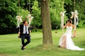 Bride in a Berta Bridal gown and groom in a navy blue Ralph Lauren tuxedo on swings with ribbons