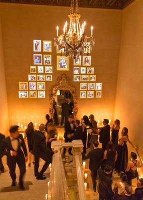Guests in formal attire walk up staircase of The Plaza Hotel with projected picture frames on wall