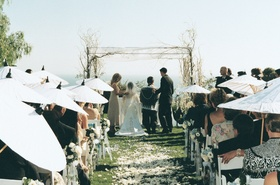Bride and groom at ceremony altar and guests on grass