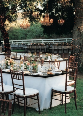 White and brown tables and chairs under trees