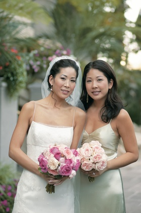 Jenny Yoo and her sister hold bouquets of pink roses and peonies