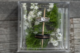 round diamond pavé band, black men's wedding ring with rose gold stripe, acrylic box with greenery
